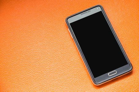 Black cell phone on orange leather background photo
