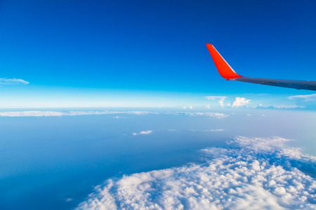 Red Wing of airplane with cloud and bluesky from window photo