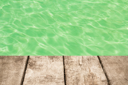 wood floor: swimming pool with sunny reflections and wood floor background Stock Photo