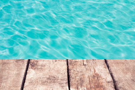 swimming pool with sunny reflections and wood floor background photo