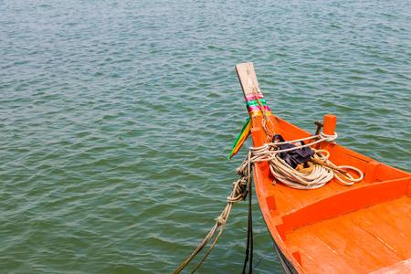 orange boat go to the sea in sunny day photo
