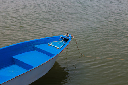 Blue and white old  boat at a the beach photo