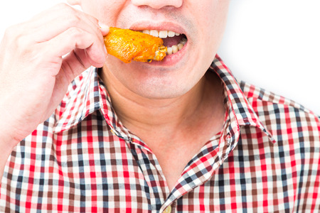 Man eating roasted chicken wings on white background photo