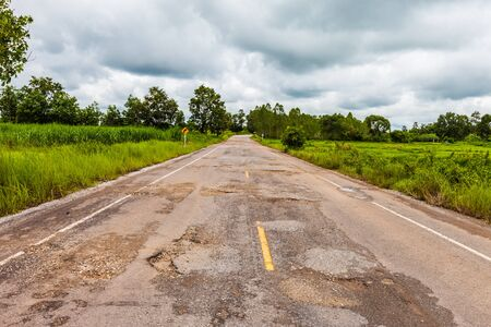 road conditions: Damaged asphalt pavement road with potholes ,Asia
