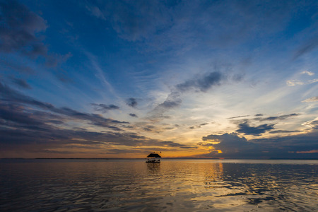 Siluate Pontoon floating in the water at sunset photo