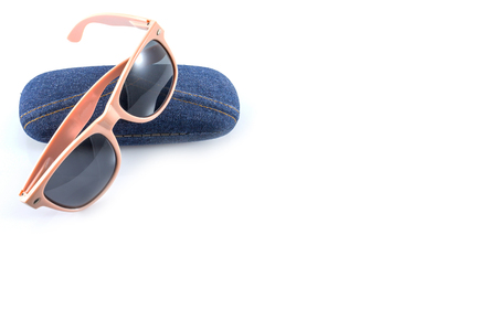 pink sunglasses in jean case on white background photo