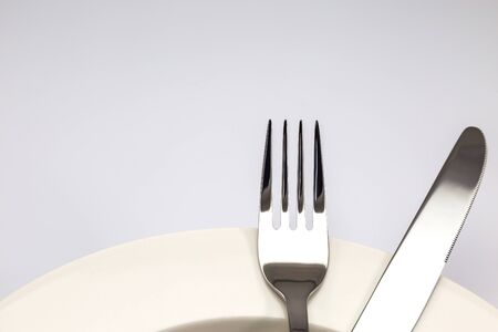 Stainless steel fork and knife on a white plate isolated on white background photo