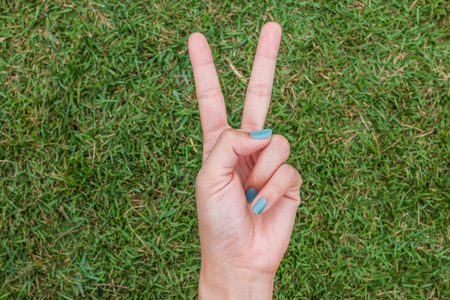 Woman hand holding up the peace sign or number two with two fingers on green grass background texture