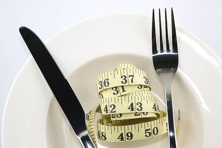 White plate with a knife and fork with measuring tape on white background, diet concept photo