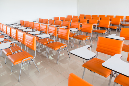 escuela edificio: aula con muchos sillones naranjas fondo Foto de archivo