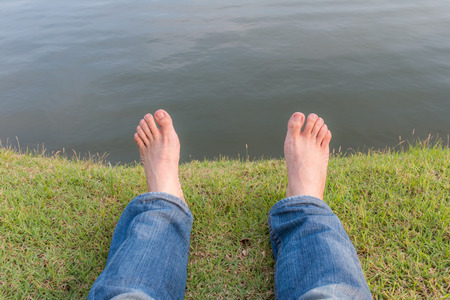 human toe: Rest and relax bare feet on green grass with lake natural background