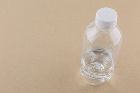 brown paper background: White water bottle on brown paper background