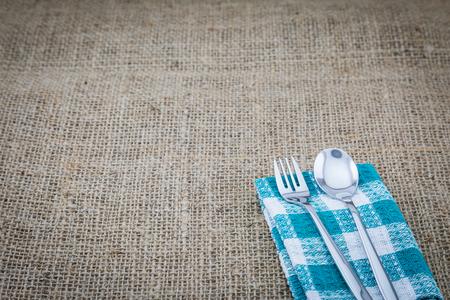 servilleta de papel: tenedor y cuchara en una servilleta verde con un fondo de saco