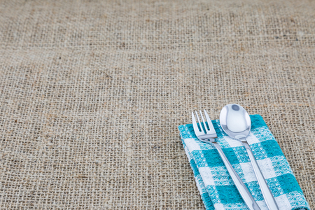 serviette: fork and spoon on a green serviette with a sackcloth background Stock Photo