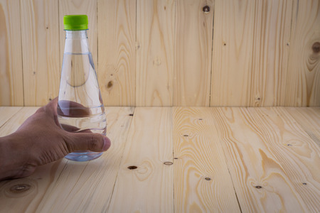 water bottles: Hand hold Drinking water bottles on a wooden floor background Stock Photo