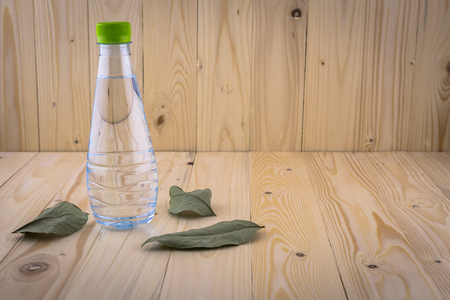 dry leaf: Hand hold Drinking water bottles on a wooden floor with dry leaf background Stock Photo