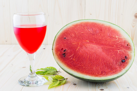 wood floor: Watermelon juice in a wine glass with half water melon on wood floor background Stock Photo