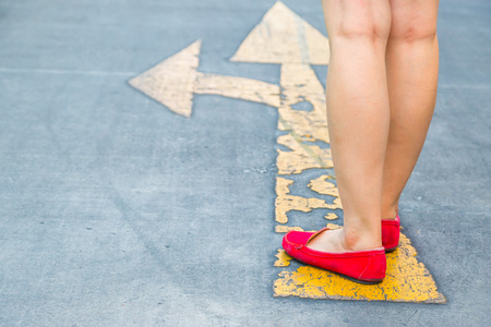 red shoes: Girl wear red shoes  walking towards with yellow traffic arrow signage on an asphalt road background