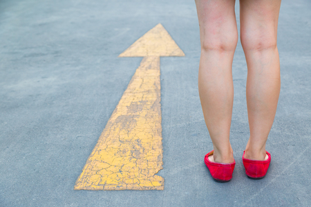 Girl wear red shoes  walking towards with yellow traffic arrow signage on an asphalt road background