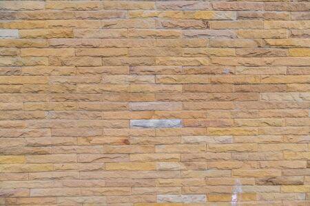 yellow stone: yellow stone wall  made with stone blocks use for background Stock Photo