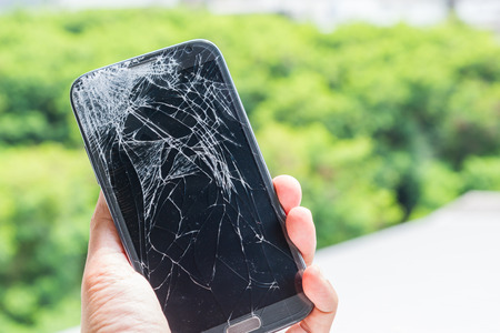 Smartphone drop to the floor and screen damage broken in hand with green bokeh background
