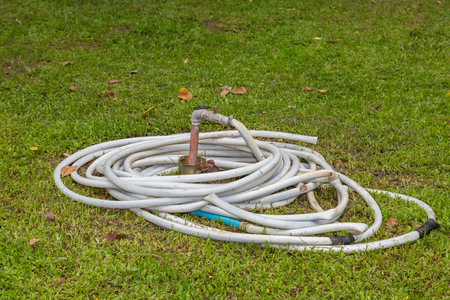 hosepipe: curled of old white hosepipe on green lawn in public park background Stock Photo