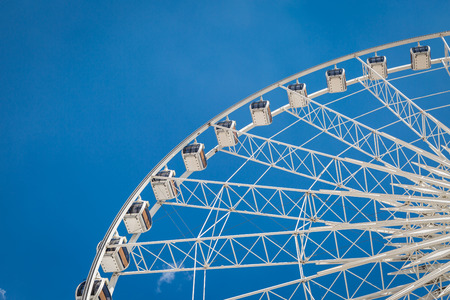 White big Ferris wheel  with blue sky sharp clouds background