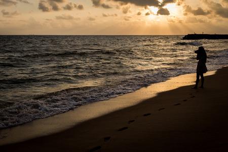 mujer sola: Solo y triste en la playa antes de fondo silueta amanecer Foto de archivo