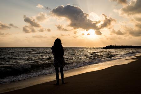 mujer triste: Solo y triste en la playa antes de fondo silueta amanecer Foto de archivo
