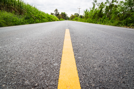 yellow line: Empty asphalt road through the agricultural fields with yellow line towards