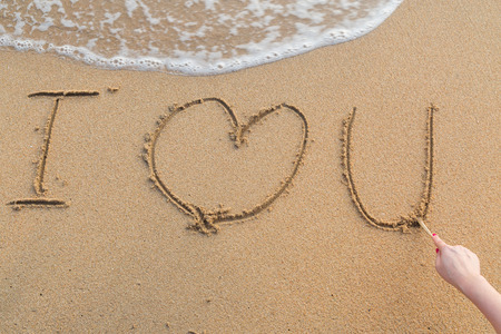 te amo: Mensaje te amo en la arena con la mano de mujer dibujo en la playa