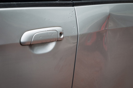 Door car with damage on accident with dent on left side on raining day