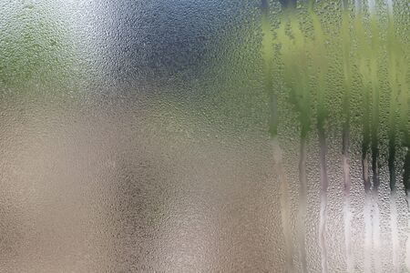 condensation on glass: Drops of water on glass with green background