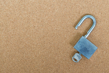 lock and key: Old master key and key lock on cork board background Stock Photo