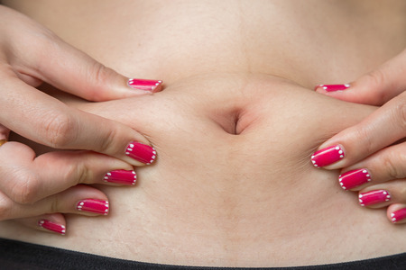 navel piercing: navel of the stomach of woman with black underwear