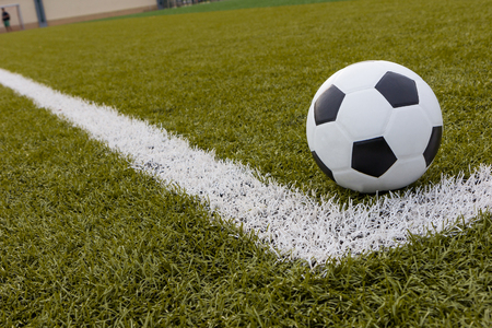 synthetic fiber: Soccer ball ,Football on artificial grass with white stripe in football stadium