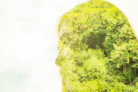 Double exposure of face woman with tree branches and leaves backfeound