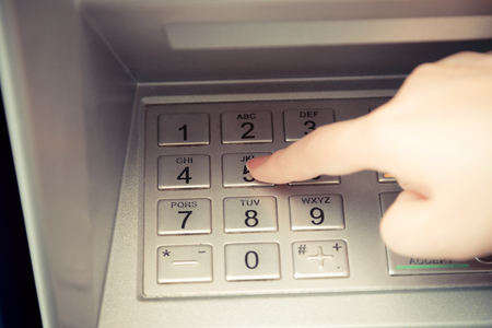 pin code: Close up of hand entering pin code at ATM machine to withdraw her money