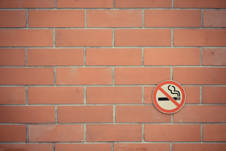 brick sign: No smoking sign on red brick background