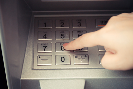 up code: Close up of hand entering pin code at ATM machine to withdraw her money