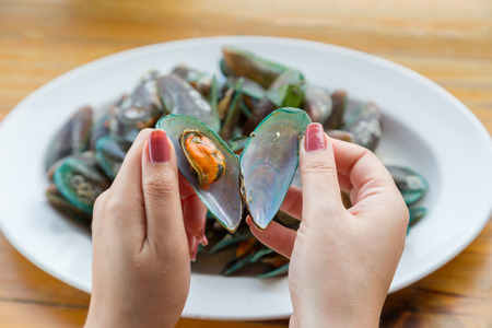 mussel: Woman hand open green mussel with white disk background