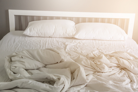 hotel bedroom: Two white pillow on bed with wrinkle messy blanket in bedroom background Stock Photo