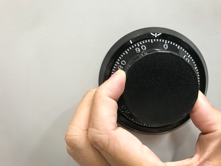 Hand is rotating the security code of safe background