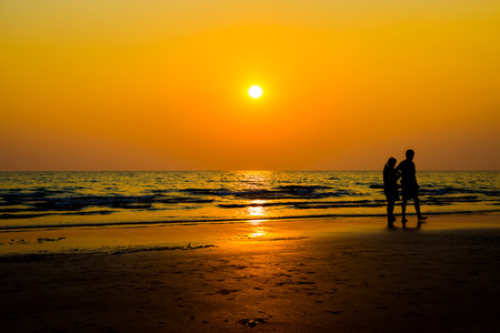 Siluate lovers and beach before sunset background