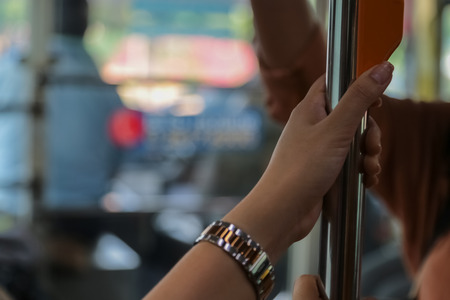 Hand holding safety straps, Hanging handle, plastic grab handle inside the public transport Stock Photo