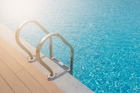 Stairs Ladder and handle down the swimming pool with blue water background