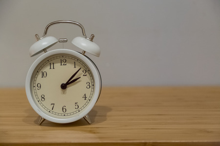Alarm clock on the wood table beside the bed background