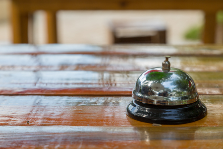 Bell on the wood table in restaurant with nature background Stock Photo