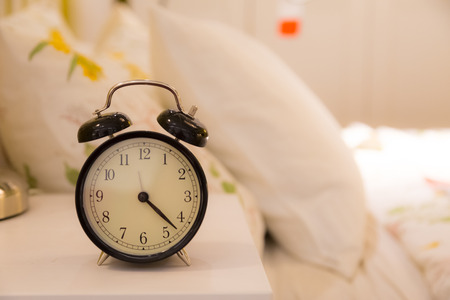 Alarm clock,on bedside with blur bed background Stockfoto