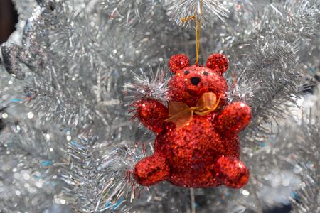 Red glitter bear on white christmas tree background